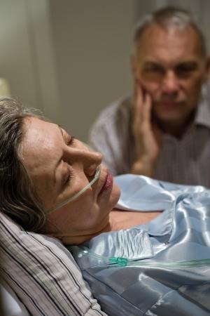 Sterbende alte Frau im Krankenhausbett mit fürsorglichen Mann Lizenzfreie Bilder