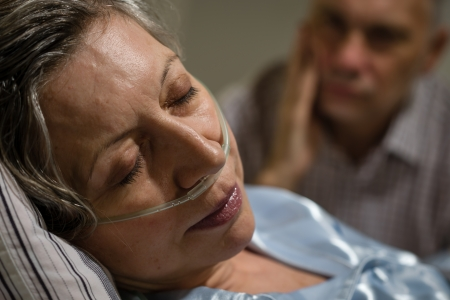 seriously: Close up of woman with nasal cannula and worried husband