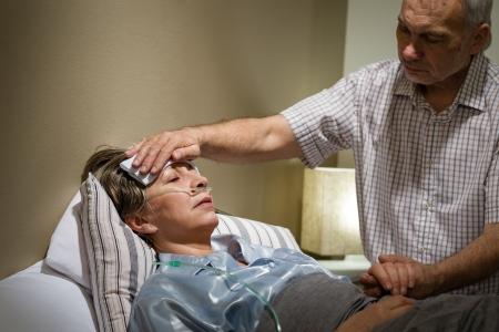 fieber: Caring Senior Menschen helfen, seine kranke Frau im Bett liegend Lizenzfreie Bilder