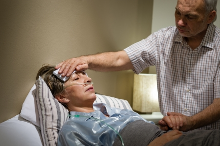 Hombre mayor cuidado ayudando a su esposa enferma en la cama