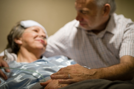 Old woman in pain lying bed holding hands with husband