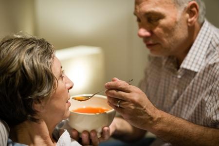 Hombre mayor que cuida la alimentación de su esposa enferma de sopa caliente Foto de archivo
