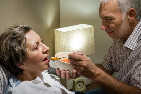 Loving marido jubilado que introduce a su esposa enferma con sopa