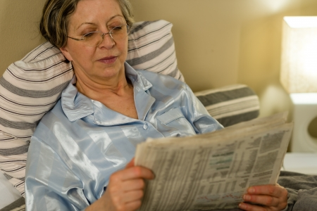Retired woman reading newspaper before sleeping in bedroom photo