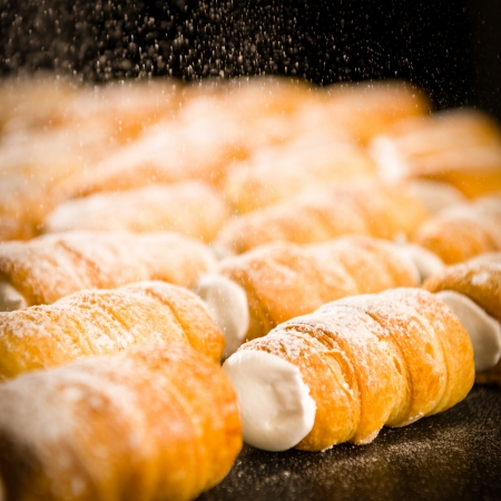 Powder sugar falling to cream horns filled with whipped cream