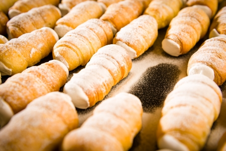 Puff pastries filled with whipped cream in powder sugar coating photo