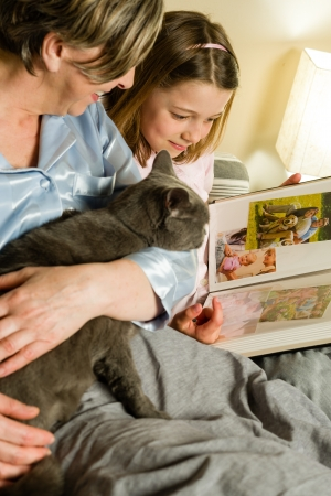 old photograph: Old woman and granddaughter spending time together looking at pictures