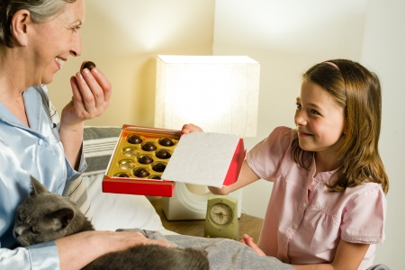 Cute granddaughter offering pralines to grandmother lying in bed photo