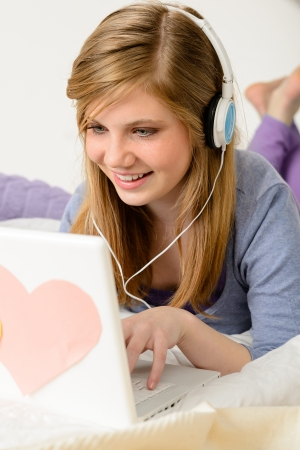 Young teenage girl chatting on laptop and lying on bed photo
