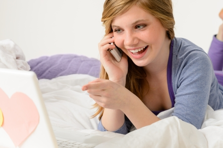 Laughing teenager relaxing by speaking on phone and using laptop photo