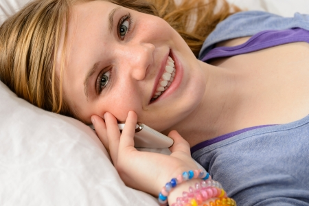 teen girl face: Portrait of a smiling teenager girl talking on her phone