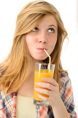 sipping: Dreamy blonde girl sipping orange juice in plaid shirt