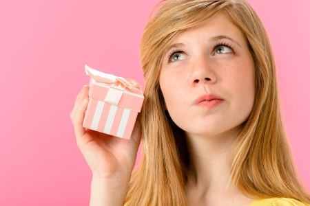 unopened: Curious girl holding unopened present isolated on pink background