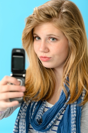 self confident: Young girl taking picture of herself with mobile phone Stock Photo