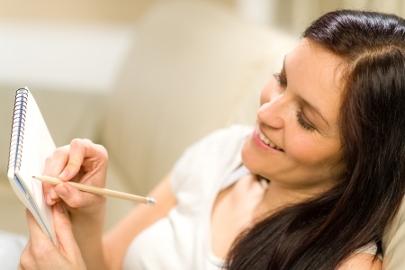 Glückliche Frau Notizen in Notizblock mit Bleistift