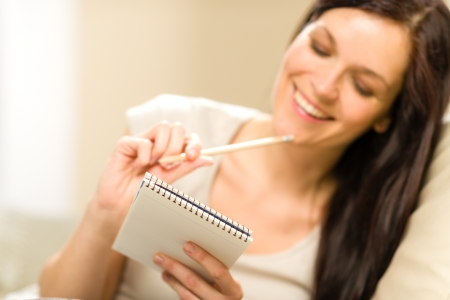 taking notes: Pensive brunette woman writing to notebook