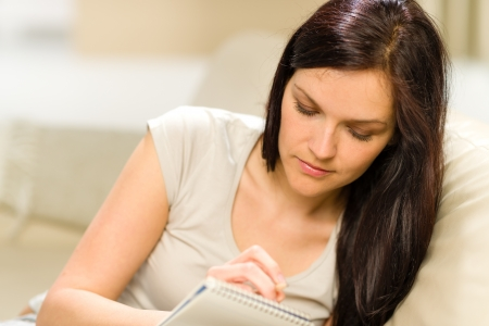 Young woman writing letter to copybook Standard-Bild