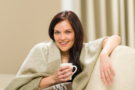 Joyful cozy woman drinking hot drink on sofa photo