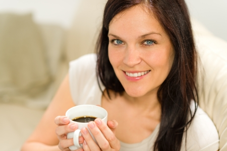 Smiling satisfied woman holding cup of espresso in cozy environment photo