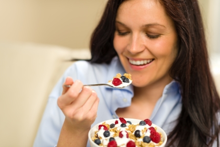 Relaxed woman eating bowl of cereal for breakfast Standard-Bild