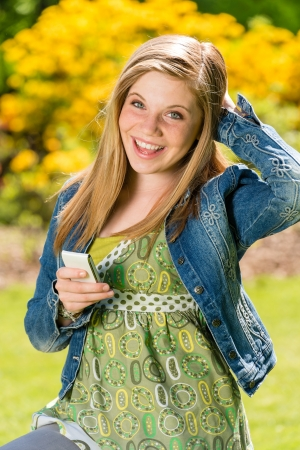 Perky female teenager texting in the park with smart phone photo