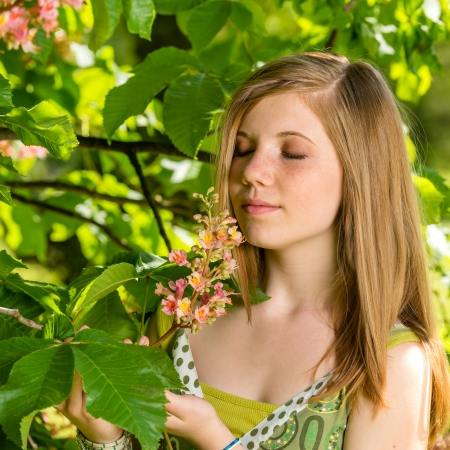 Young girl smelling blossom of the tree springtime Stock Photo