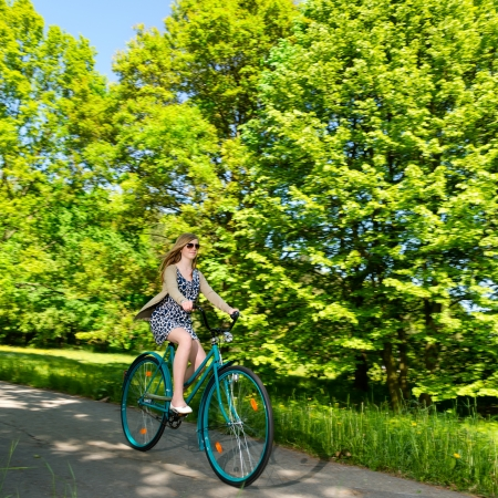 Happy woman riding fast her bicycle in the sunny park photo