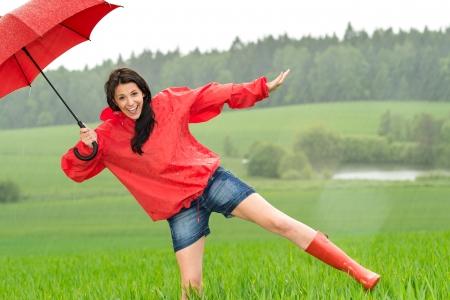 Speels gelukkig meisje in de regen met rode paraplu