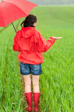 wellies: Woman standing in raincoat and with umbrella on the field
