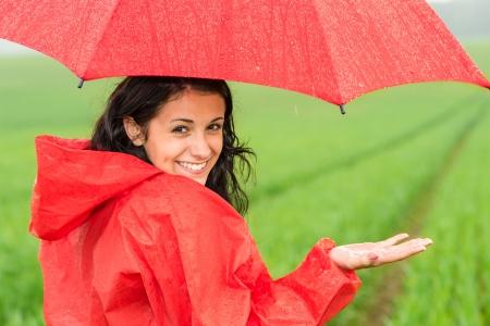 Chica adolescente Lively bajo la lluvia mirando a la cámara