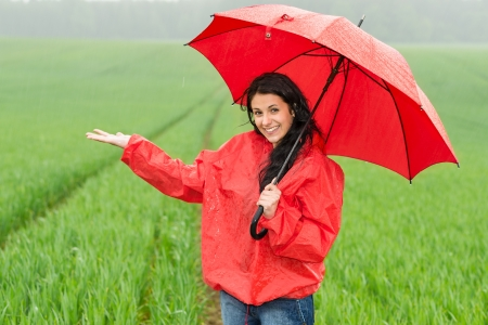 Elated smiling girl during rainy weather outside with umbrella Standard-Bild