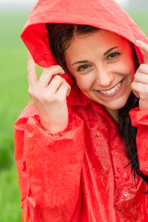 Portrait of cheerful teenager in the rain in red raincoat photo