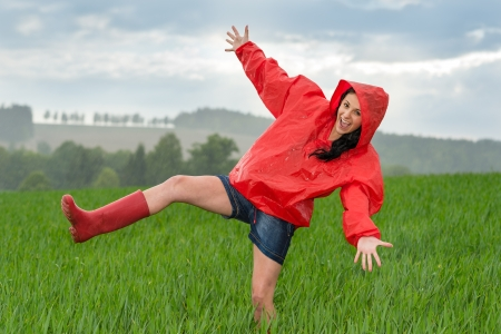 rubber boots: Playful teenage girl dancing in the rain on a field