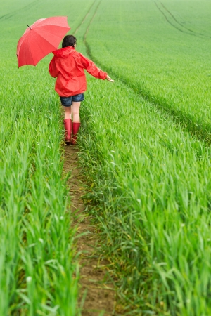Lonely girl walking in the rain in rubber boots photo