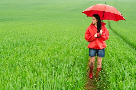 downpour: Smiling young woman standing on meadow on rainy day