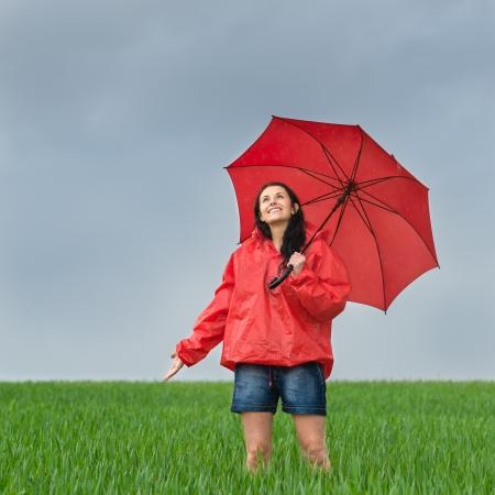Carefree girl enjoying rain shower outdoors looking up photo