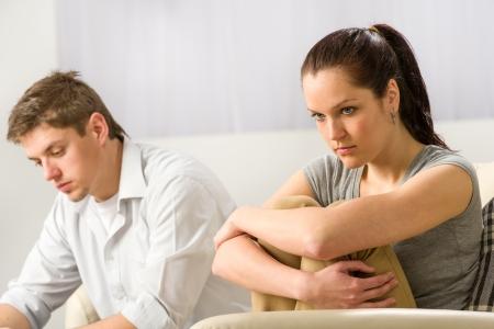 Pareja infeliz que se sienta en el sofá en silencio tras una discusión
