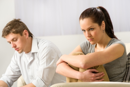 people arguing: Unhappy couple sitting on couch silently after argument