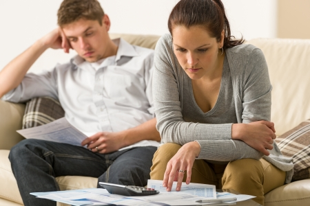 budget crisis: Annoyed couple calculating their finances during recession Stock Photo