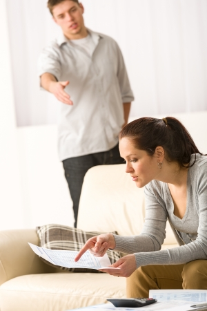 Fighting couple over bills and tax in their living room Stock Photo - 20142188