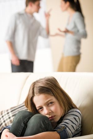 Triste petite fille et les parents de combat en arrière-plan Banque d'images