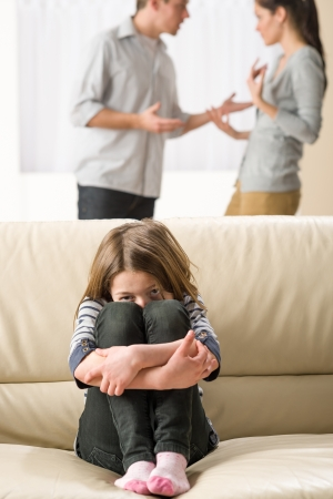 Scared little girl sitting on the couch listening to parents argument photo