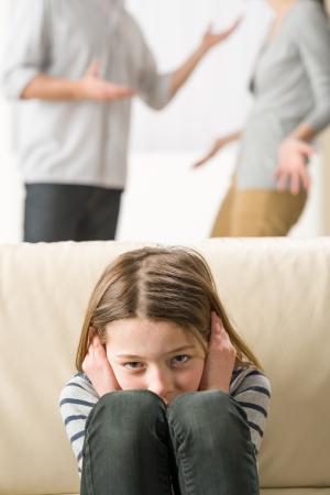 problemas familiares: La niña está preocupado porque los padres argumentando Foto de archivo