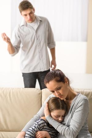 personas discutiendo: Madre proteger a su hija de padre enojado y violento Foto de archivo