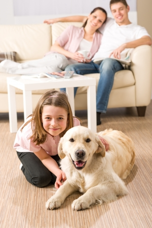 A happy family of three sitting with dog photo