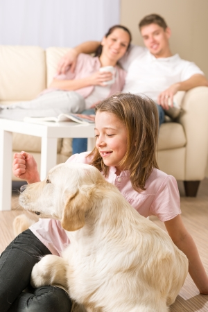 family on couch: Playful girl petting family dog with parents sitting on couch