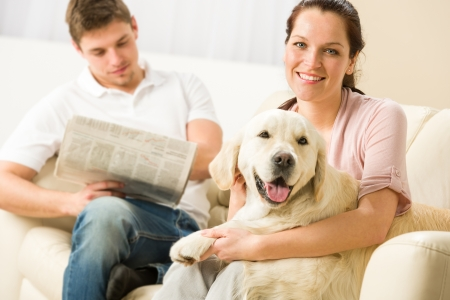 Resting joyful couple sitting and petting dog man reading newspaper Stock Photo - 20142161