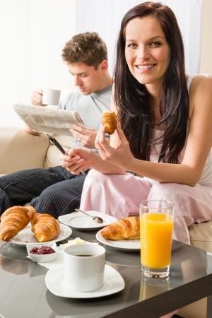 Smiling couple eating romantic breakfast in hotel room photo