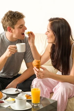 Carefree couple eating breakfast in pajamas at home photo