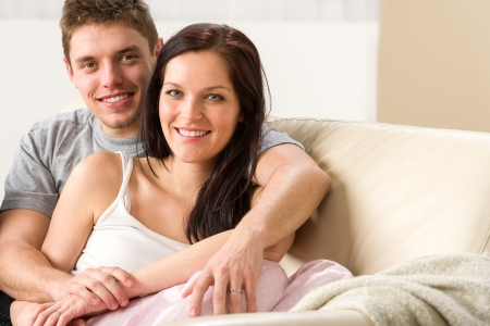 Carefree young couple embracing each other on couch Stock Photo - 20142185